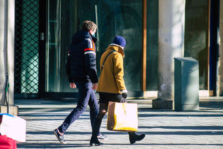 Reims France January 09, 2021 View of unidentified pedestrian with a face mask to protect themself from the coronavirus walking in the streets of Reims during the pandemic affecting France Editorial
