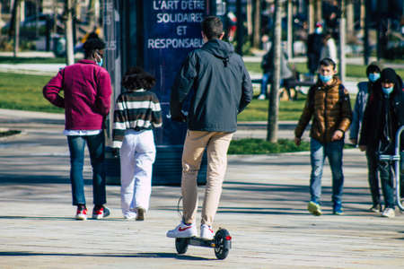 Reims France March 03, 2021 People rolling with an electric scooter in the streets of Reims, operating with a small utility internal combustion engines and a deck in the center Sajtókép