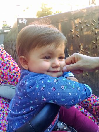 Cute little baby. She is smiling in her stroller, while her cheek is being pinched.