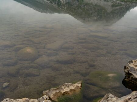 Lake with rocks in its depths. You can see reflections from the mountains around.