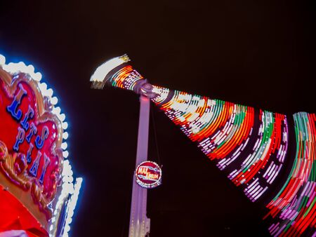 Fairground ride in motion. It is night time and everything is illuminated.