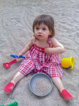 One-year-old baby sitting quietly on the floor of a porch while nibbling on a small twig.