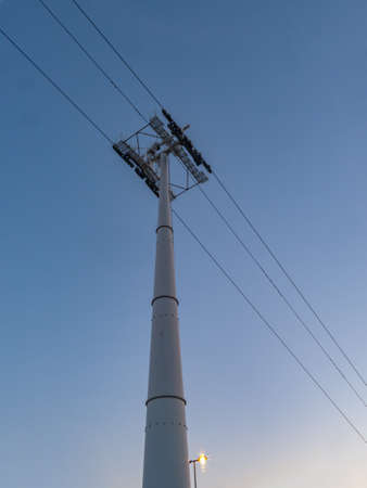 Power tower on a clear blue sky at night, with a lighted street lamp in the background