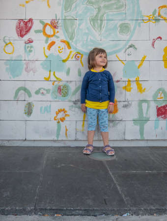 Four-year-old girl smiling standing next to a hand-painted mural on a white wall, as she watches