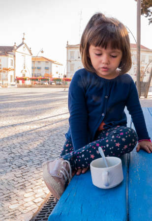 Little girl dressed in a cardigan and star-spangled pants drinking a cup of chamomile tea on a cobblestone street bench