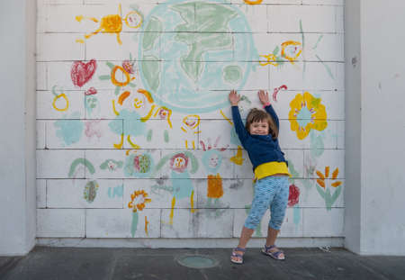 Four-year-old girl playing happily next to a hand-painted mural on a white wall
