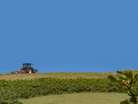 Tractor working in the field, lonely under a completely blue summer sky