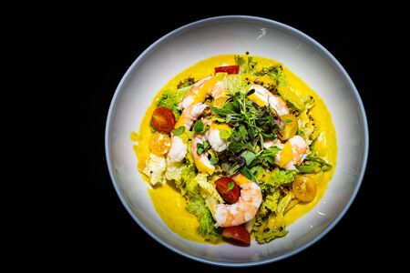 a birds eye view of a amazing tropical prawn and avocado salad with a lemon and herb dressing and mixed leaves