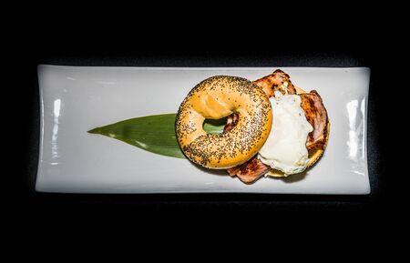 a tasty breakfast bagel filled with egg, sausage and bacon to start the day Stock fotó