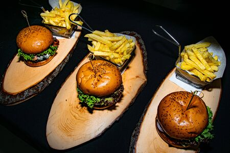 a triple portion of beef burgers served with fries on a wooden tree trunk plate