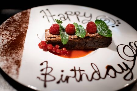 a amazing chocolate brownie decorated with raspberrys and mint leaves and happy birthday written in chocolate Reklamní fotografie
