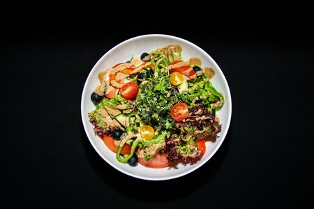 a traditional mixed green salad with mixed leaves, sliced peppers and cherry tomatoes