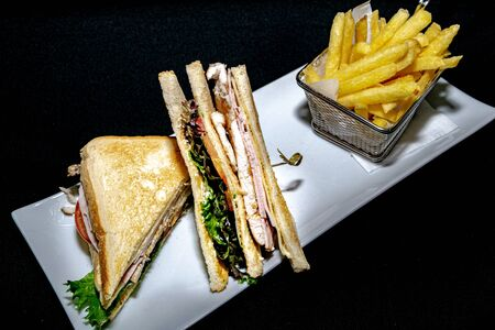 a tasty toasted club sandwich filled with grilled chicken, turkey ham and salad served along side French fries Zdjęcie Seryjne
