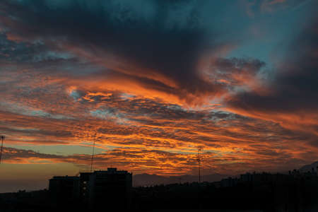 the last golden clouds being lit from behind a silhouetted cityscape in Marbella, Spain 免版税图像