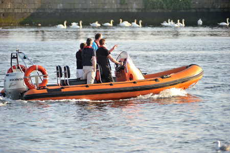 Galway Spanish Arch , Ireland June 2017,River Corrib , Group of people Sailling a Inflatable boat with motor