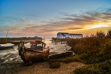 Abandoned boat by the sea shore in low tide