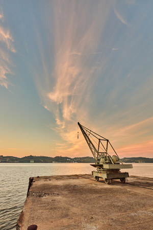 machinery: Tower crane holding by the river harbor at sunrise