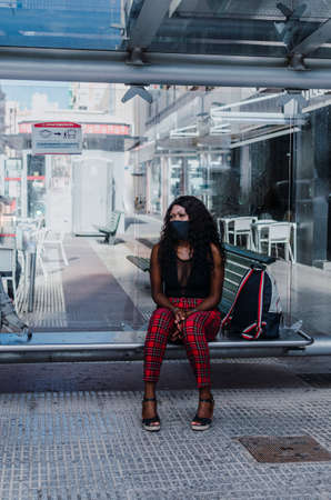 African girl sitting on bus stop bench waiting to be picked up