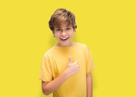 Cheerful boy puts thumb up to say everything is fine