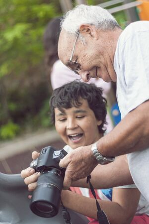 grandfather and grandson sharing photos laughing, enjoying in the park. laughter and joy. Photography. happy moments