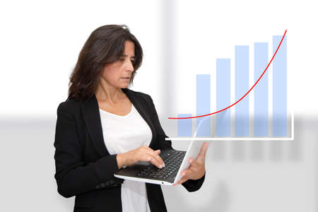 An attractive middle-aged woman works on her laptop. It seems that according to the charts everything is a success in your business. Positivism. Things are going very well