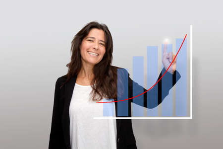 Attractive laughing middle-aged woman points a finger at charts of her business success. Positivism. Things are going very well
