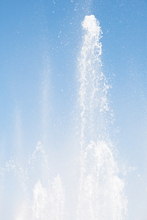 fountainhead: Water fountain on blue sky view from below in sunny day