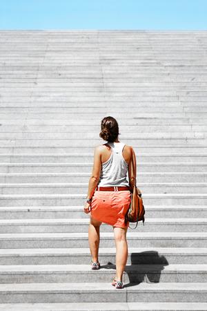 upstairs: Young woman going upstairs. Challenge metaphor. Stock Photo