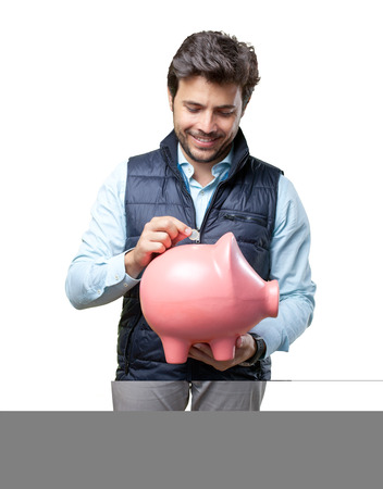 Man with vest insert coin on pig Imagens
