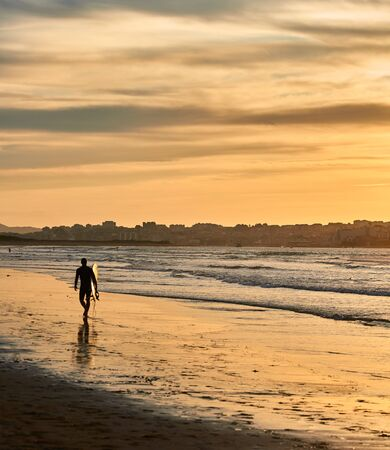 A surfer walking on the beach in a nice sunset
