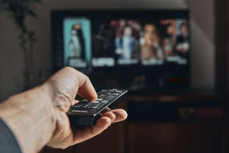 A man's hand zapping on television Stock Photo