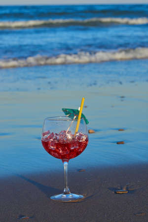 A delicious and refreshing cocktail on the sand of the beach near the waves.