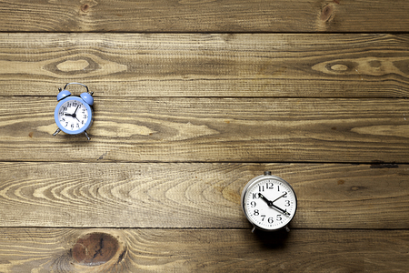 two alarm clocks  on wooden background