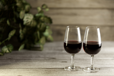 two glass of red wine with unfocused plant on wooden table Imagens