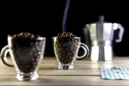 two coffee cups filled with coffee beans and italian coffeemaker on wood table and black background Archivio Fotografico