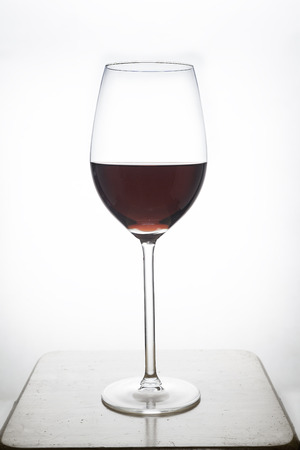 glass of  red wine on wood with white background