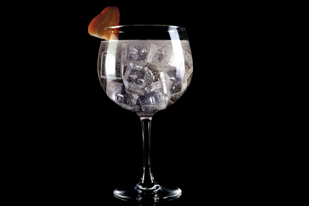 Gin tonic and strawberry on elegant black background