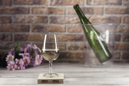 white wine glass on mini pallet with green bottle in ice bucket and flowers on wood table and bricks background