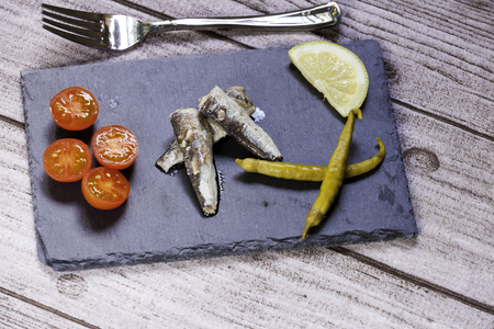 appetizercanned sardines, cherry tomatoes, green chilli pepper and  lemon slice on slate dish