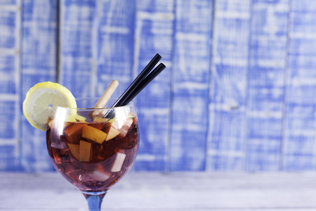 spanish sangaree cup close-up with raw fruits, cinnamon sticks, black drinking straw and lemon slice on wood table and blue wood background