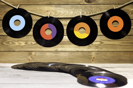 four vinyl singles hanging with clothespins on a string on wooden background and vinyl singles on top of a wooden table
