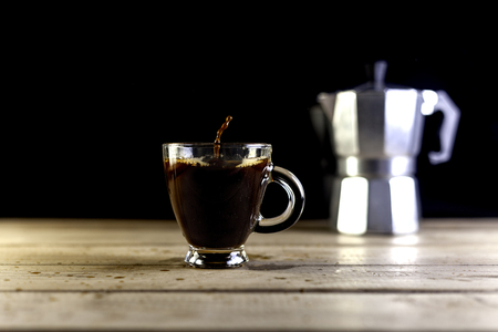 Cup of coffee with coffee drop and italian coffeemaker on wood table and black background