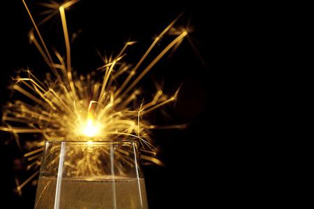 champagne glasses close-up with lit sparkler on black background