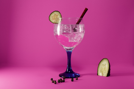 gin tonic with cucumber slice, cinnamon stick and pepper on pink background