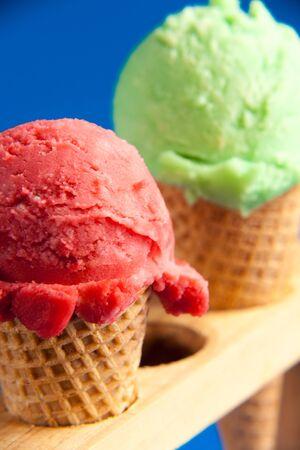 two ice cream cornet close-up green and strawberry colour on blue background Foto de archivo