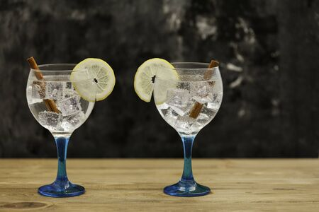 Two gin tonics on blue glass with lemon slice and cinnamon sticks on wooden table and dark backdrop