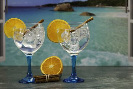 two gin tonics on blue glass with orange slice, orange and cinnamon sticks on dark table and beach backdrop 版權商用圖片