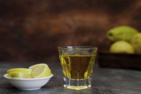 tequila shot with lemon slice and lemon basquet on brown fantasy background Foto de archivo