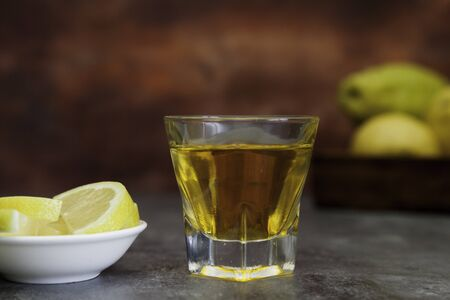 tequila shot with lemon slice and lemon basquet on brown fantasy background close-up