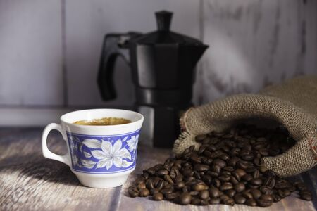 cup of coffee, coffee beans coming out of a sack and italian coffee maker on wooden table